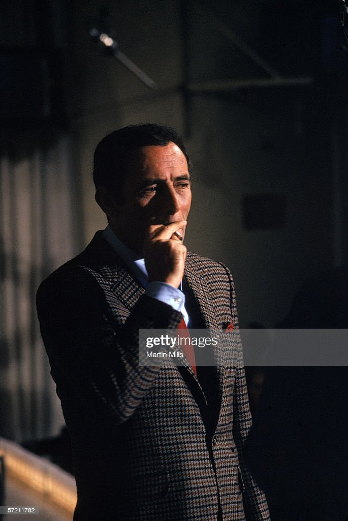 American actor comedian Joey Bishop smokes a cigarette as he stand on the set of his show 'The Joey Bishop Show' in Los Angeles, California.
