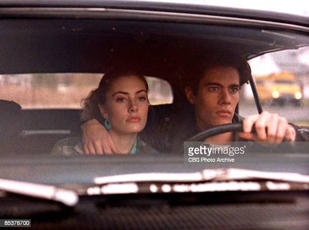 American actor Dana Ashbrook steers a car from behind the steering wheel with his other arm around the shoulders of actress Madchen Amick in a scene...