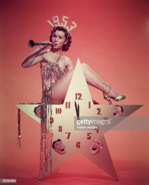 American actor dancer and singer Debbie Reynolds wearing a 1953 tiara and a costume with tinsel blows a horn while sitting atop a starshaped clock in...