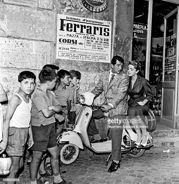 American actor Dean Martin is on board a Vespa with Italian/born American actress and soprano Anna Maria Alberghetti while a group of children...