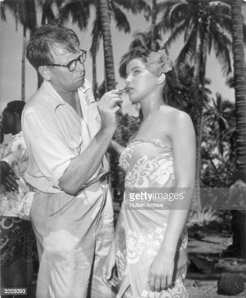 American actor Debra Paget stands while makeup artist Dick Smith applies her lipstick in front of tall palm trees on the set of director Delmer...