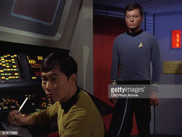 American actor DeForest Kelley as Dr Leonard 'Bones' McCoy stands behind American actor George Takei as Sulu in a scene from 'The Man Trap' the...