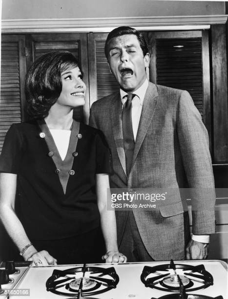 American actor Dick van Dyke makes an exaggerated crying face as he wears a suit in front of the stove in the kitchen set alongside American actress...