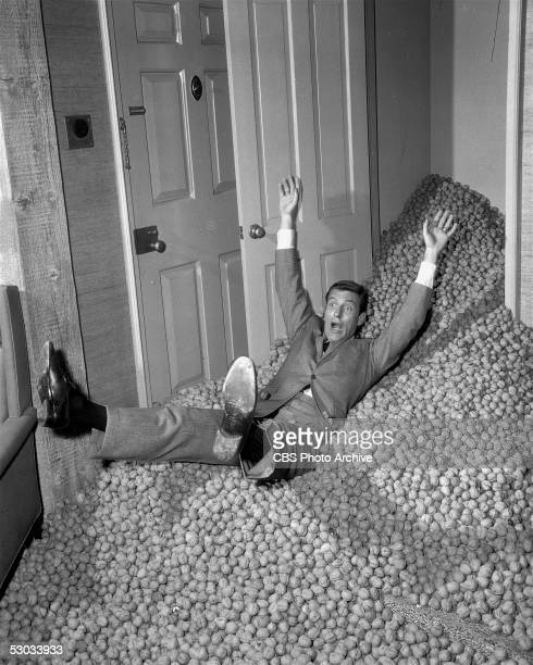 American actor Dick Van Dyke slips and falls on a pile of nuts as they come tumbling out of a closet in a scene from an episode of the television...