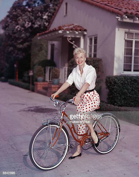 American actor Doris Day poses on a red Schwinn bicycle late 1950s