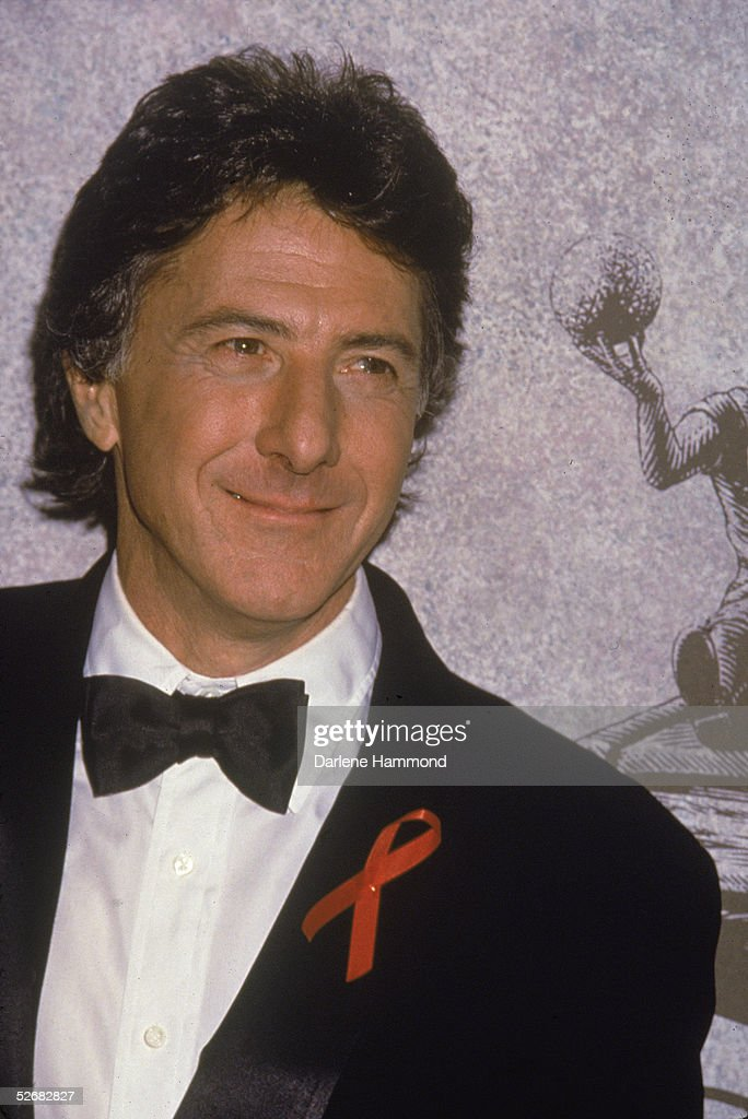 American actor Dustin Hoffman poses in a tuxedo at a formal event, mid 1990s. He wears a red AIDS awareness ribbon on his lapel.