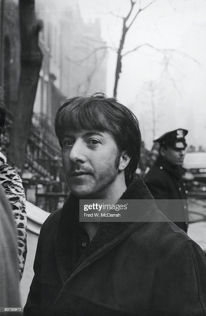 American actor Dustin Hoffman stands with onlookers on a smoke-filled street as firefighters battle the flames from an explosion in the basement of 18 West 11th Street, New York, New York, March 6, 1970. Hoffman own house, 16 West 11th Street, was next door to the Greenwich Village house was being used by members of the Weathermen (later Weather Underground) and the explosion, caused by the accidental detonation of a bomb during its construction, resulted in three deaths.