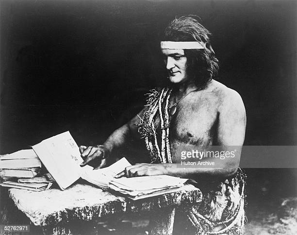 American actor Elmo Lincoln as Tarzan teaches himself to read in a scene from the silent film 'Tarzan of the Apes' directed by Scott Sidney 1918