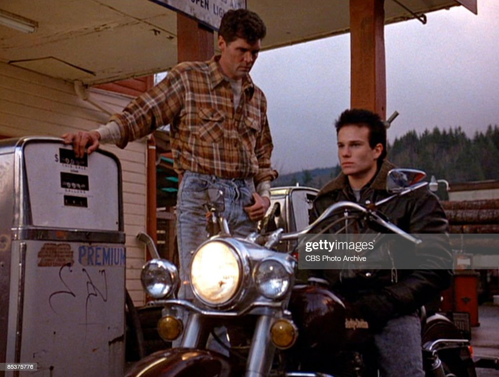 American actor Everett McGill (as Big Ed Hurley) stands beside a fuel pump in a gas station as actor James Marshall (as James Hurley) sits astribe a motorcycle in a scene from the pilot episode of the television series 'Twin Peaks,' originally broadcast on April 8, 1990.