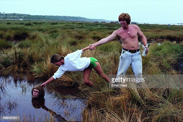 American actor Everett McGill up to his neck in a pond whilst filming the quicksand scene for 'Quest for Fire' 1980