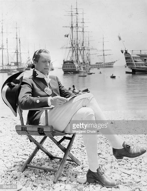 American actor Franchot Tone studies his script on the beach of old Portsmouth harbour between takes of the MGM film 'Mutiny on the Bounty' Behind...