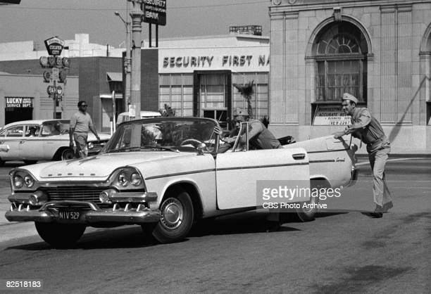 American actor Frank Sutton and Jim Nabors push a convertible along a street in a scene from an episode of the television comedy series 'Gomer Pyle...