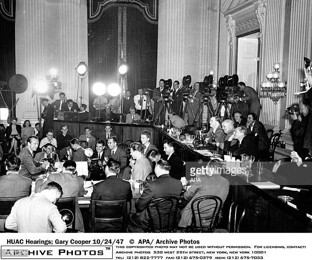 American actor Gary Cooper is shown on the stand and beaming for the cameras during a moment of levity at the House UnAmerican Activities Committee...