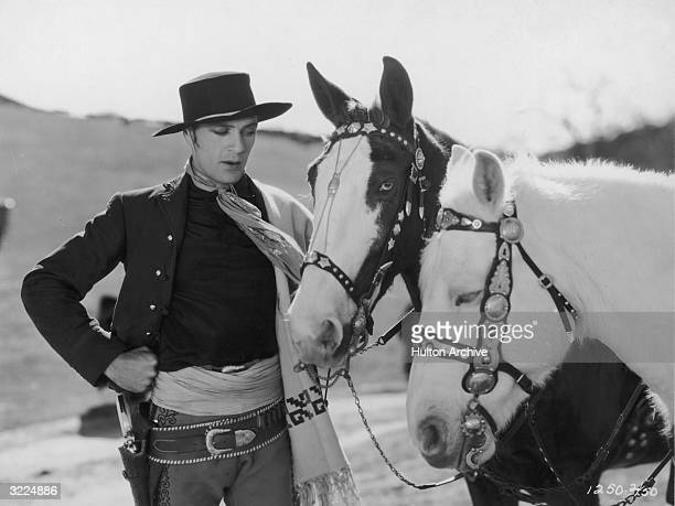 American actor Gary Cooper stands with one hand on his hip talking to two horses in a scene from director John Cromwell's film 'The Texan' He wears a...