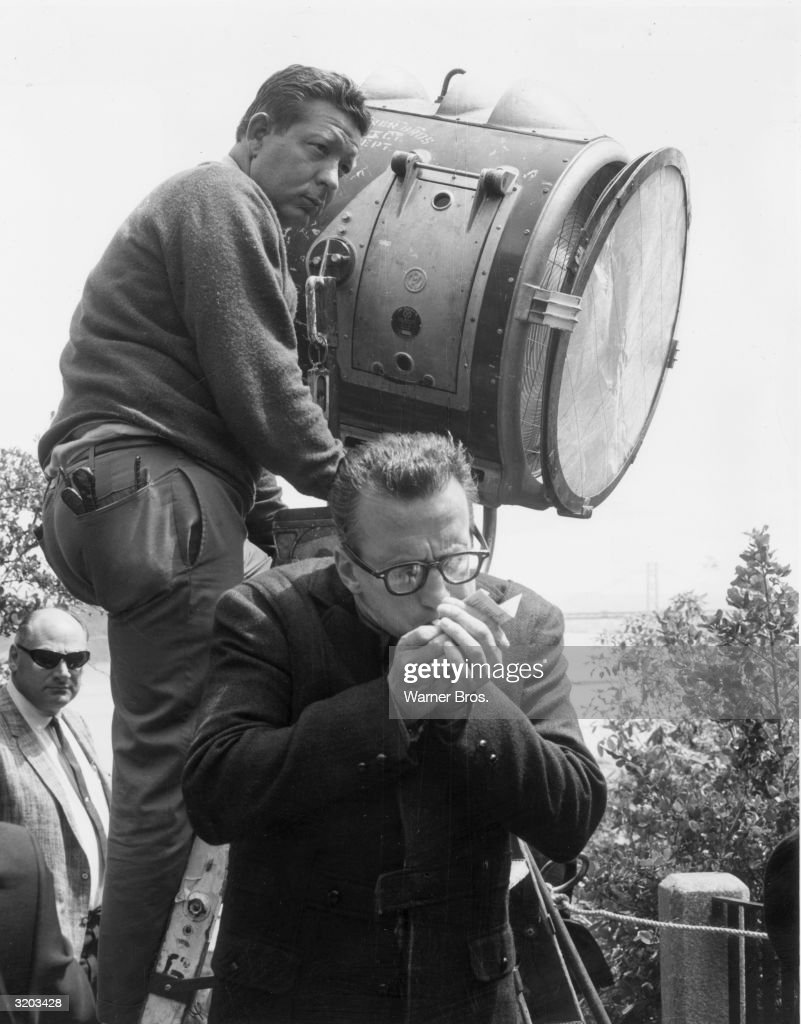 American actor George C Scott (1927 - 1999) cups his hands while lighting a cigarette in front of a spotlight outdoors on the set of director Richard Lester's film, 'Petulia'.