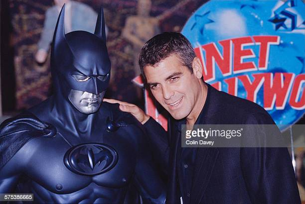 American actor George Clooney poses with a model of Batman during a photocall for his latest film 'Batman and Robin' at Planet Hollywood London UK...
