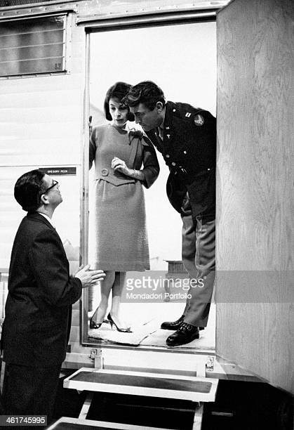 American actor Gregory Peck and his wife Veronique Peck leaning out of a caravan and talking to a technician on the set of Captain Newman MD...