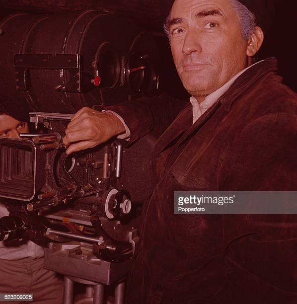 American actor Gregory Peck pictured dressed in character as Catalan guerilla Manuel Artiguez standing next to a camera during the production of the...