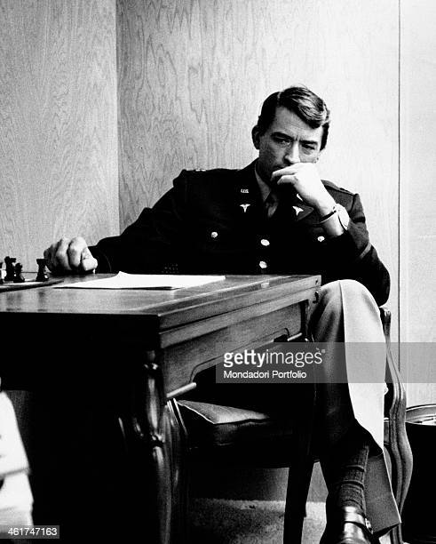 American actor Gregory Peck relaxing seated at a table inside his caravan while shooting the film Captain Newman MD Hollywood 1963