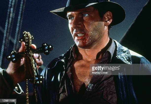American actor Harrison Ford as the eponymous archaeologist in a scene from the film 'Indiana Jones and the Last Crusade' 1989 Here he traces the...