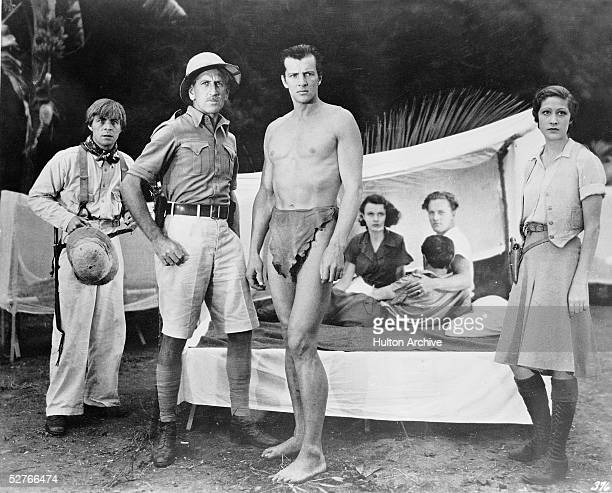 American actor Herman Brix as Tarzan and other cast members stand in their camp and watch with some concern events offcamera in a scene from 'Tarzan...