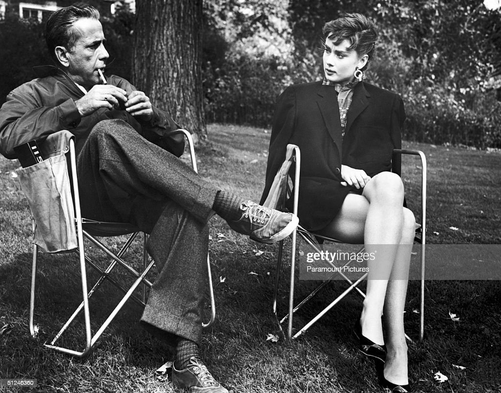 1954, American actor Humphrey Bogart, lighting a cigarette, and Belgian-born actor Audrey Hepburn outdoors on the set of director Billy Wilder's film 'Sabrina'.
