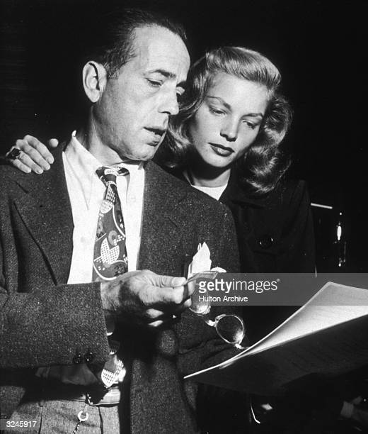 American actor Humphrey Bogart points at a script with his eyeglasses while his wife American actor Lauren Bacall reads over his shoulder