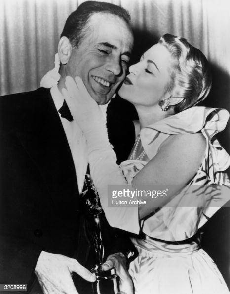American actor Humphrey Bogart receives a kiss from actor Claire Trevor while standing backstage with the Best Actor Oscar he won for his role in...