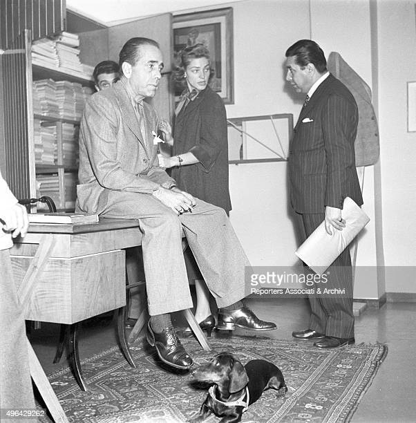 American actor Humphrey Bogart sitting on a writing desk in the Battistoni tailor's shop with the American actress Lauren Bacall and the Italian...