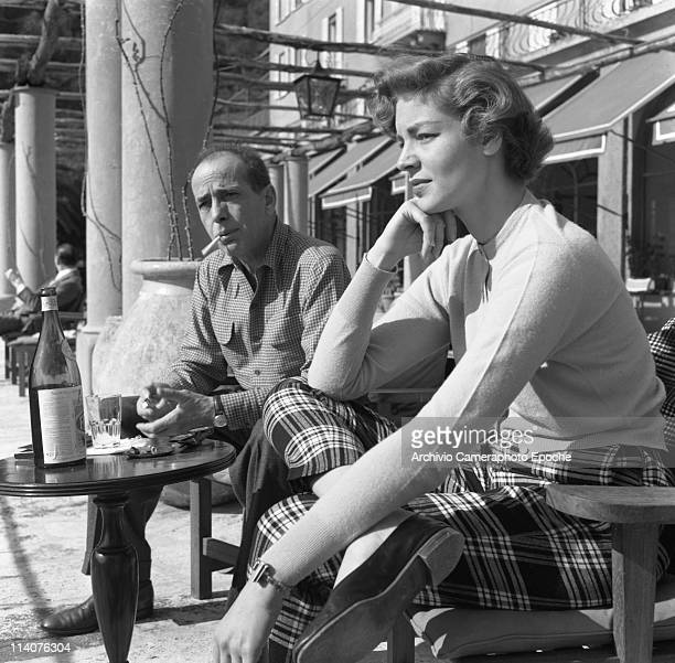 American actor Humphrey DeForest Bogat with his wife Lauren Bacall sitting outside a cafe in Portofino1954 He is wearing a checked shirt and he's...