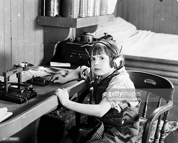 American actor Jackie Coogan using an electric telegraph machine in a scene from a movie 1924