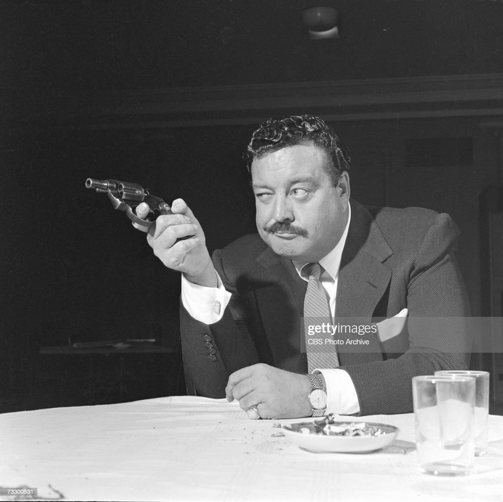 American actor Jackie Gleason (1916 - 1987) casually aims a gun as he sits at a table in the CBS television Playhouse 90 production of 'The Time of Your Life,' September 3, 1958.