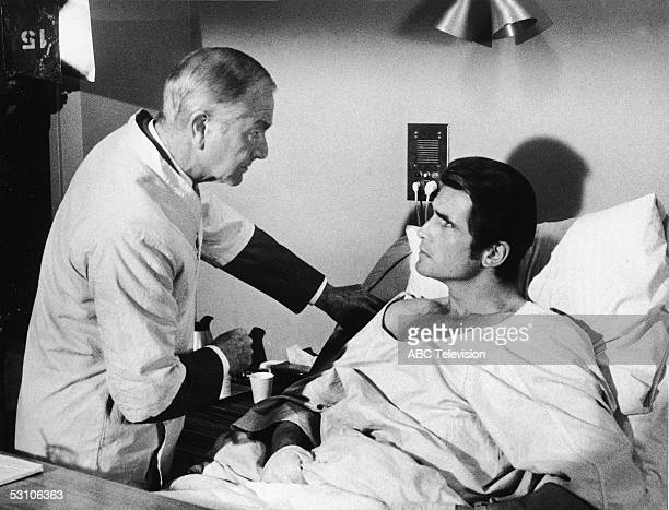 American actor James Brolin lies in a hospital bed while American actor Robert Young dressed in doctor's scrubs worn over a suit stands over him in a...