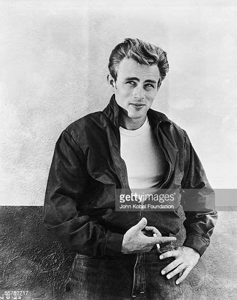 American actor James Dean leaning against a wall on the set of director Nicholas Ray's film 'Rebel Without a Cause' 1955