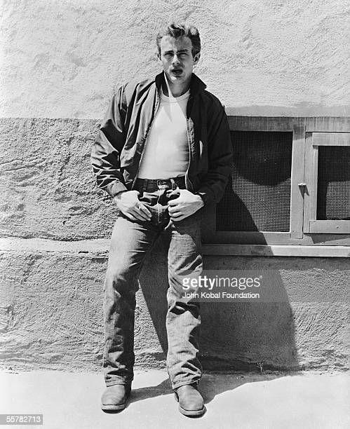 American actor James Dean leans against a wall on the set of director Nicholas Ray's classic film 'Rebel Without a Cause' 1955