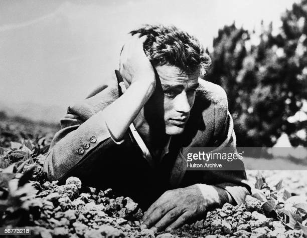 American actor James Dean lies in the dirt with his head leaning on his hand 1950s