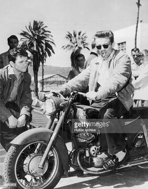 American actor James Dean sits on a motorcycle with a cigarette in his mouth as young male and female fans look on