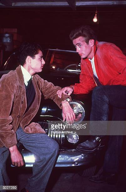 American actor James Dean stands with his foot on the front fender of a car while touching actor Sal Mineo's arm in a still from director Nicholas...