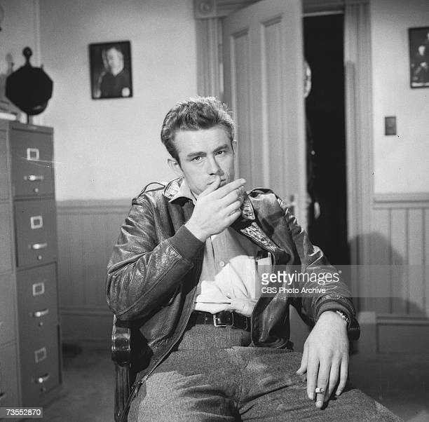 American actor James Dean wears a leather bomber jacket and smokes a cigarette as he sits in a chair during the episode 'The Unlighted Road' of the...