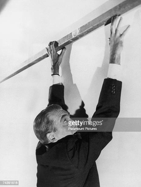 American actor James Stewart hangs from a perilously high ledge in a publicity still for 'Vertigo' directed by Alfred Hitchcock for Paramount 1958