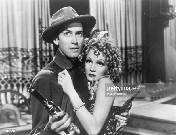 American actor James Stewart wields two pistols as Germanborn actor and singer Marlene Dietrich clings to him fearfully in a still from director...