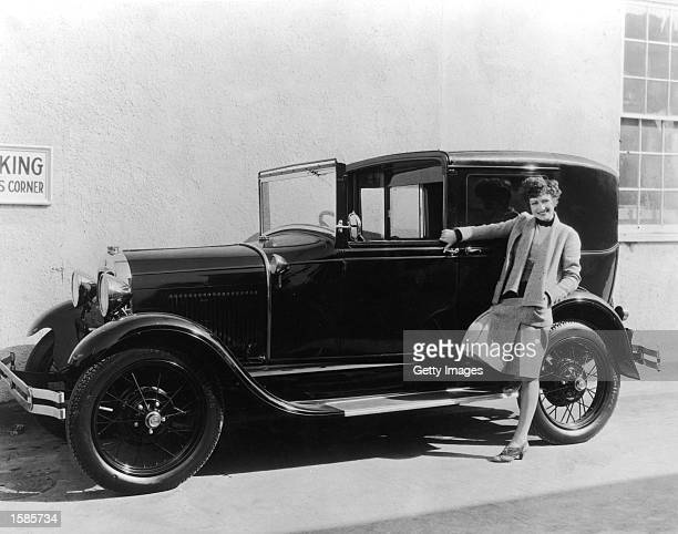 American actor Joan Crawford leans against an early model Ford c 1927