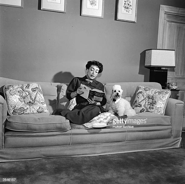 American actor Joan Crawford sits on a sofa reading a book with her pet poodle 1940s