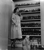 American actor Joan Crawford stands with her poodle looking at her large shoe closet 1940s