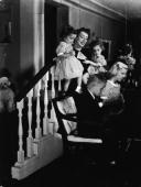 American actor Joan Crawford watches her son Christopher and daughter Christina play the piano while holding her twin daughters Cindy and Cathy at...