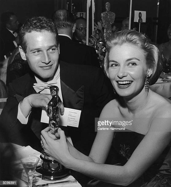 American actor Joanne Woodward holds her Oscar statuette while sitting next to husband American actor Paul Newman during the Governor's Ball an...
