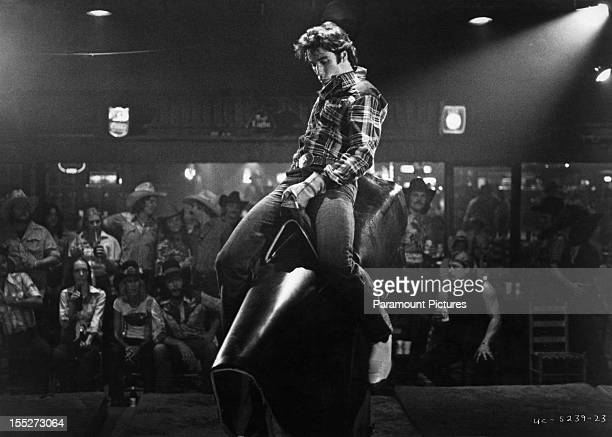 American actor John Travolta rides a bucking bronco machine in a scene from the film 'Urban Cowboy' 1980