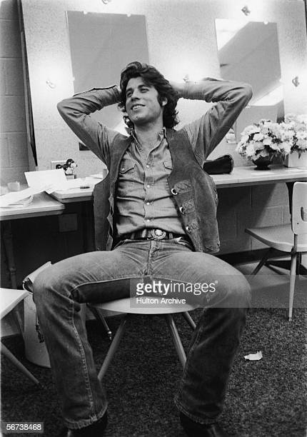 American actor John Travolta sits in a chair and leans back with his hands behind his head late 1970s