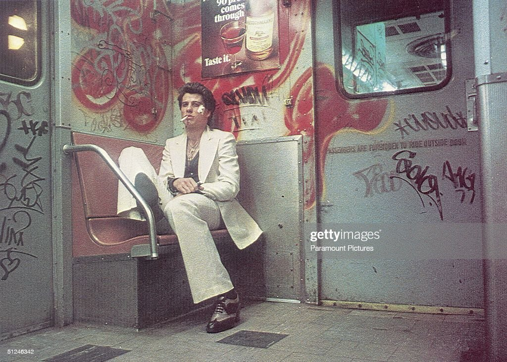 1977, American actor John Travolta sits on a bench inside a subway car painted with graffiti in a still from director John Badham's film 'Saturday Night Fever'.