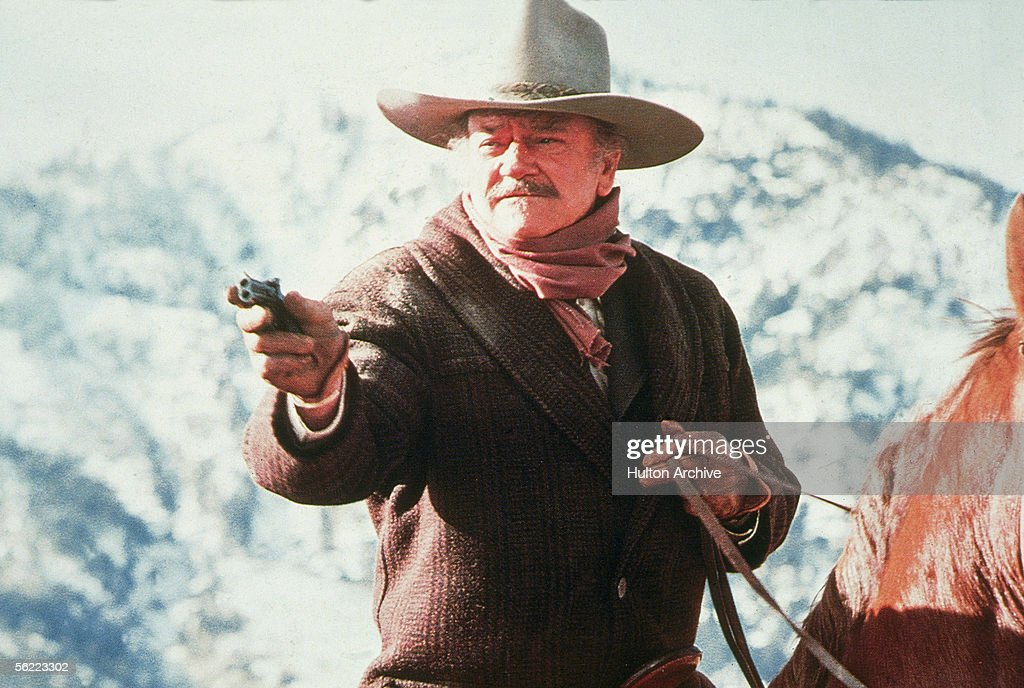American actor John Wayne aims a gun while riding horseback in a scene from 'The Shootist' 1976 'The Shootist' the story of a dying gunfighter living...
